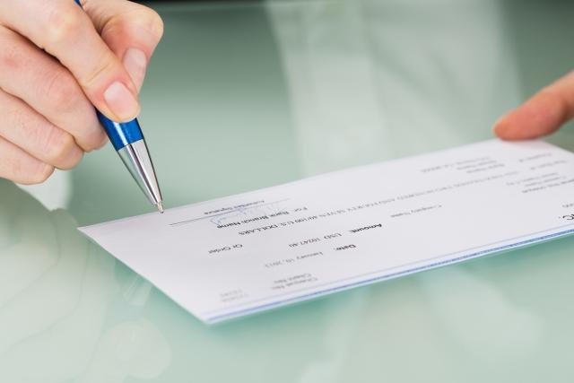 Businesswoman Hand Signing Cheque